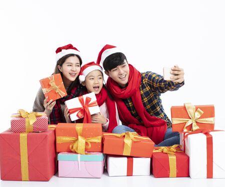 Happy family holding Christmas gift taking selfie
