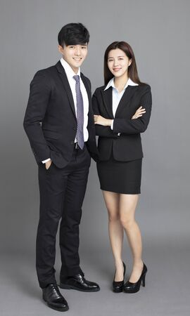 young business man and woman standing against gray background Reklamní fotografie - 129625703