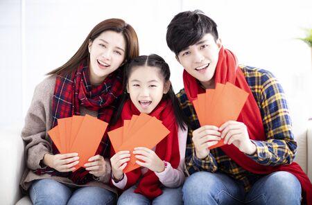 feliz familia asiática mostrando sobre rojo para el año nuevo chino Foto de archivo