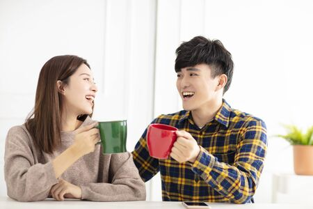Happy young couple holding tea cup looking at each other