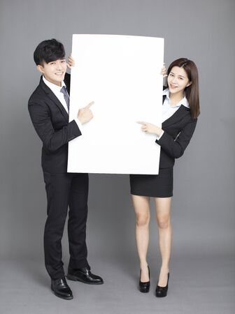 young business man and woman showing blank billboard  against gray background Reklamní fotografie - 129625850