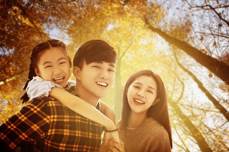 happy asian family  with autumn leaves background Reklamní fotografie - 129778230