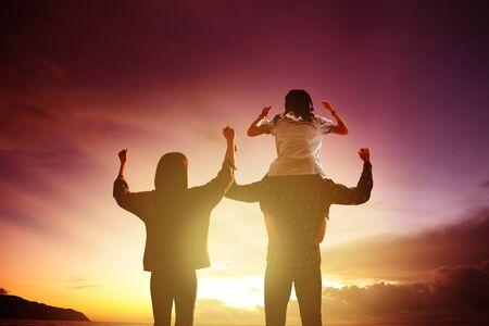vista trasera familia de pie y mirando la puesta de sol