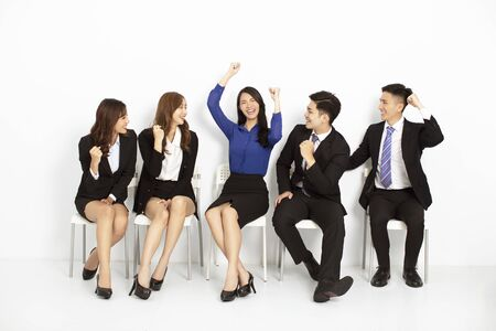 happy asian business people sitting on the chairs in a row