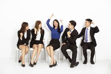 szczęśliwi azjatyccy ludzie biznesu siedzący na krzesłach w rzędzie