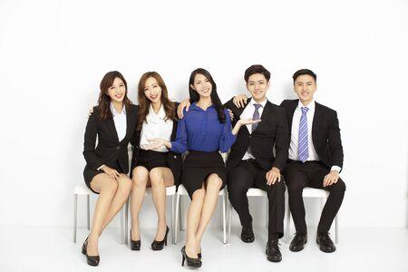 Retrato de empresarios asiáticos sentados en las sillas en una fila