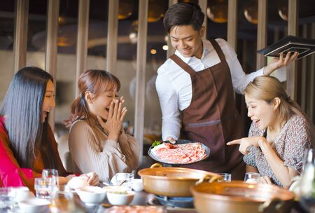 Happy waiter bring beef slices and serving group of friends in restaurant. Imagens