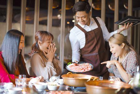 Szczęśliwy kelner przynosi plastry wołowiny i obsługuje grupę przyjaciół w restauracji. Zdjęcie Seryjne