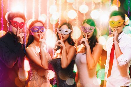 young group celebrating New Year on masquerade party