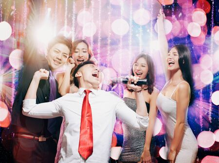 happy young group singing and dancing in party Stock Photo