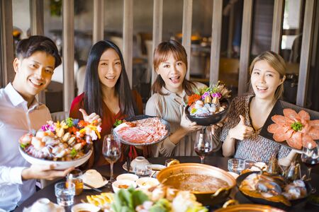 Jeunes amis montrant des tranches de bœuf et de porc aux fruits de mer dans un restaurant de fondue