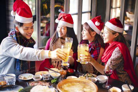Happy friends having fun and celebrating christmas in hot pot restaurant 版權商用圖片 - 130783663
