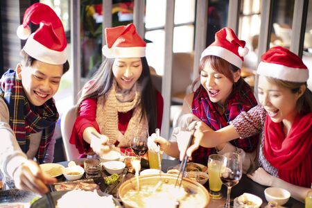 Happy friends having fun and celebrating christmas in hot pot restaurant