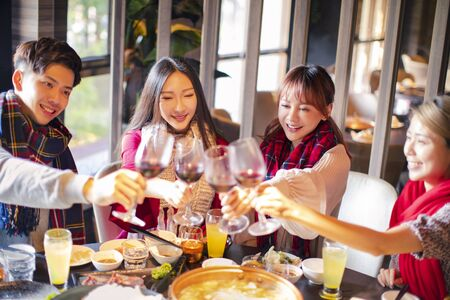 Happy friends having fun in hot pot restaurant