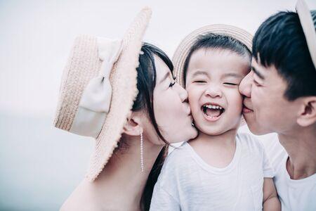 happy parents kissing the little boy