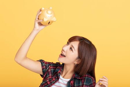 young asian woman  checking the  piggy bank