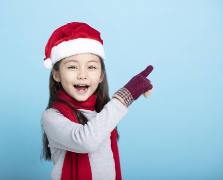 happy little girl in Santa hats and pointing at something
