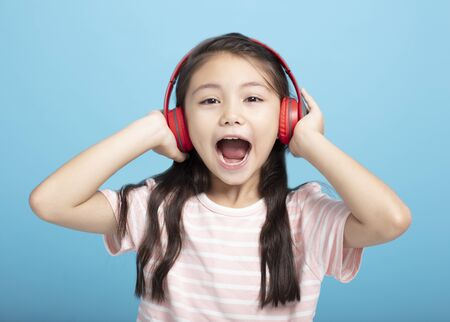 happy little girl with headphones listening and singing song