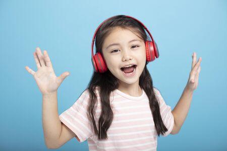 glückliches kleines Mädchen mit Kopfhörern, das Lied hört und singt