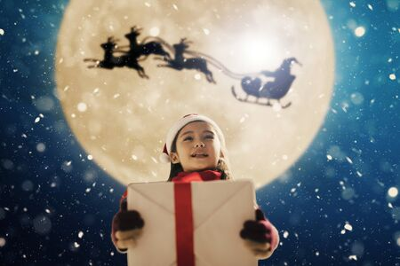 Cute little girl with christmas presents. Santa Claus flying in  moon sky