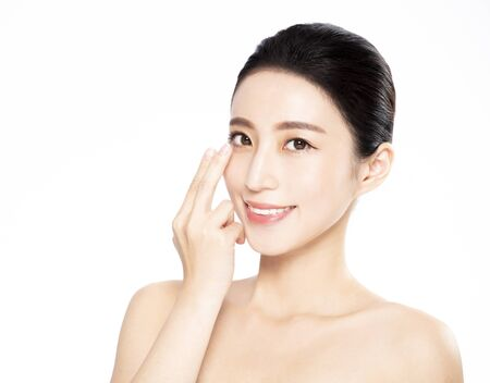Young woman putting contact lens in her eye Stock Photo