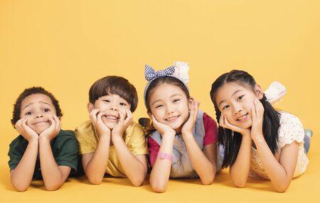 Glückliche Kinder, die zusammen auf dem Boden liegen