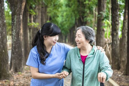 Smiling nurse helping senior woman to walk around the park Zdjęcie Seryjne
