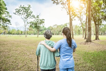 nurse helping senior woman to walk around the park