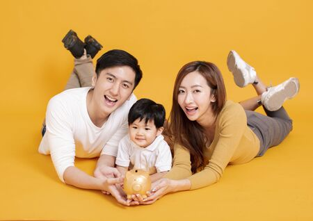 happy young family holding piggy bank