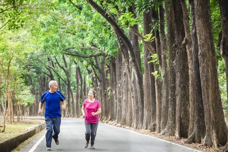 happy asian Senior couple running outside at park Stock fotó