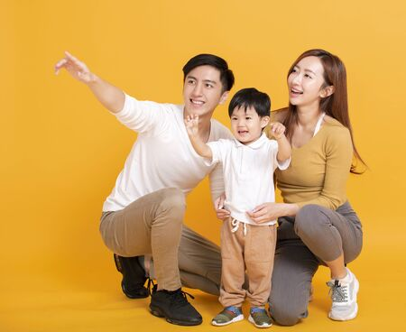 Happy asian family looking away and pointing