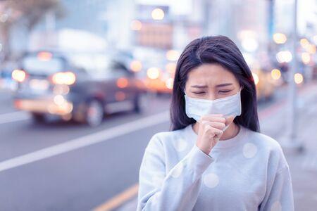 Mujer joven usar máscara en la ciudad durante el día del smog