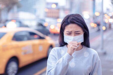 une jeune femme porte un masque dans la ville pendant le jour du smog