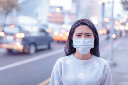 Mujer joven usar máscara en la ciudad durante el día del smog Foto de archivo