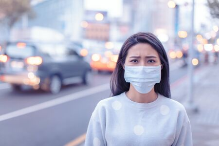 young  woman wear mask in the city during Smog day 版權商用圖片 - 134582322