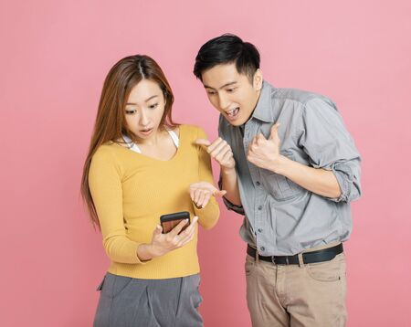 Shocked young couple watching the  smart phone