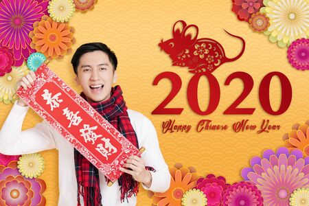 asian young man celebrating for chinese new year. chinese text happy new year 2020