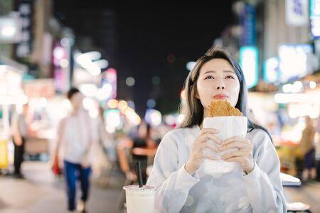 Asian woman enjoy  Chicken Fillet with street food in  Night Market Фото со стока
