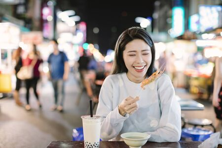 Asian young woman enjoy street food in Night Market