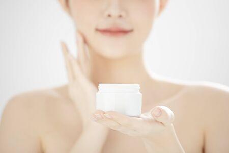 young woman holding moisturizer cream jar