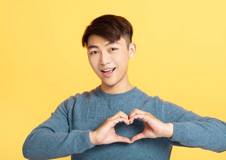young Man showing hand sign heart on his chest