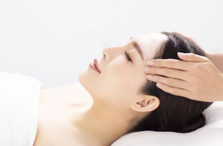 closed young woman face and head massage in spa