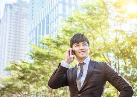 asian young businessman talking on mobile phone