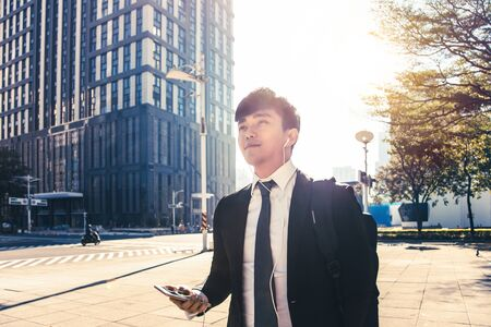 Businessman holding mobile phone while walking on street to office