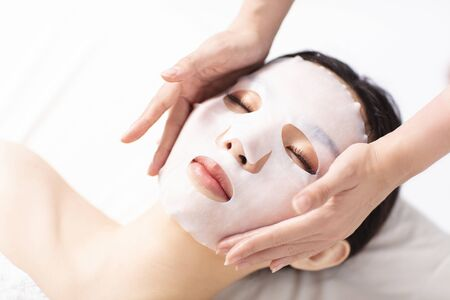 Young beauty with facial mask in spa salon