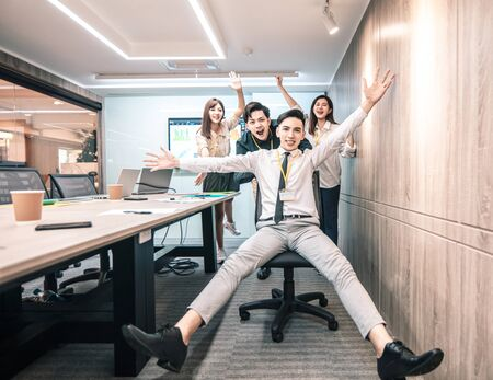 business people having fun riding on chairs in office