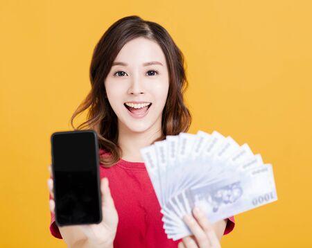 glückliche junge Frau, die Handy und Geld hält.