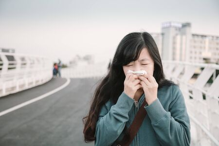 Sick  woman with cold and flu  walking  on the street  Stock Photo