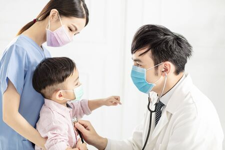 medical doctor examining little boy in clinic
