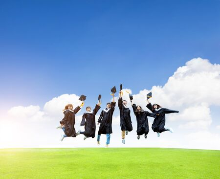 happy students in graduation gowns celebrating and jumping on the grass field